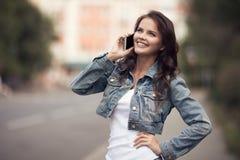 Giovane donna che comunica sul telefono Via della città su fondo Immagine Stock