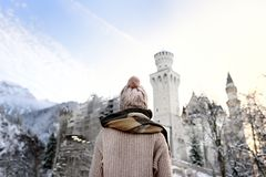 Giovane donna che considera castello reale famoso il Neuschwanstein nel giorno di inverno Fotografia Stock