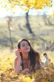 Giovane donna che contempla in foglie Immagini Stock Libere da Diritti