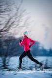 Giovane donna che corre all'aperto un giorno di inverno freddo Fotografia Stock Libera da Diritti