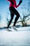Giovane donna che corre all'aperto un giorno di inverno freddo Immagini Stock Libere da Diritti