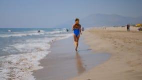 Giovane donna che corre giù la spiaggia sabbiosa stock footage