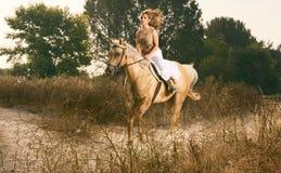 Giovane donna che corre sul cavallo (sfuocatura di movimento) Fotografia Stock