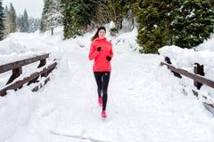 Giovane donna che corre sulla neve in montagne di inverno che indossano i guanti caldi dell'abbigliamento in tempo della neve immagini stock libere da diritti