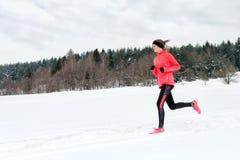 Giovane donna che corre sulla neve in montagne di inverno che indossano i guanti caldi dell'abbigliamento in tempo nevoso fotografie stock