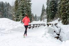 Giovane donna che corre sulla neve in montagne di inverno che indossano i guanti caldi dell'abbigliamento in tempo nevoso immagini stock