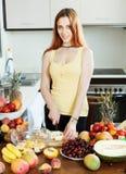 Giovane donna che cucina con i frutti maturi Fotografie Stock Libere da Diritti