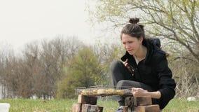 Giovane donna che cucina il barbecue della carne su fuoco durante il picnic sulla natura archivi video