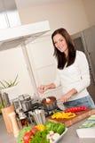 Giovane donna che cucina la salsa di pomodori nella cucina fotografie stock libere da diritti