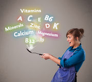 Giovane donna che cucina le vitamine ed i minerali Fotografia Stock