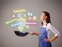 Giovane donna che cucina le vitamine ed i minerali Immagini Stock