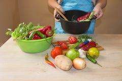 Giovane donna che cucina nella cucina Alimento sano Immagine potata delle verdure di taglio della ragazza per alimento Immagini Stock