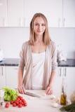 Giovane donna che cucina nella cucina Fotografia Stock