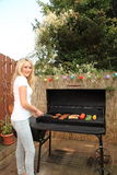 Giovane donna che cucina su un barbecue all'aperto Immagine Stock