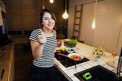 Giovane donna che cucina un pasto sano in cucina domestica Facendo cena sulla fresa facente una pausa di induzione dell'isola di  fotografia stock libera da diritti