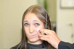 Giovane donna che dà al parrucchiere uno sguardo dubbio fotografie stock libere da diritti