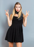 Giovane donna che dà il segno di pace fotografia stock