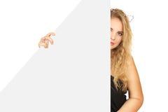 Giovane donna che dà una occhiata da dietro l'annuncio Fotografia Stock