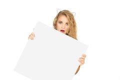 Giovane donna che dà una occhiata da dietro l'annuncio Fotografia Stock Libera da Diritti