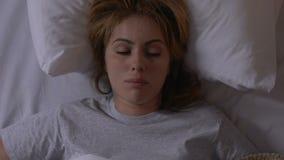 Giovane donna che decolla coperta, appena svegliante nella mattina, programma di sonno archivi video