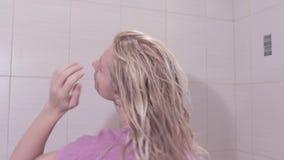 Giovane donna che decolla un asciugamano dalla sua testa e che scuote i suoi capelli bagnati in bagno video d archivio