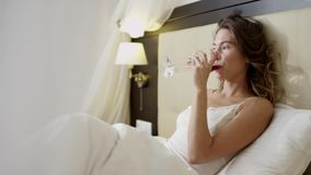 Giovane donna che discute a fondo cellulare mentre trovandosi a letto con un vetro di vino rosso archivi video