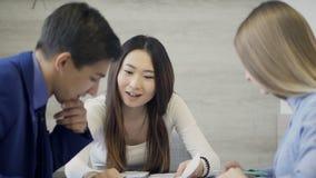 Giovane donna che discute progetto comune con i colleghi dentro l'ufficio archivi video