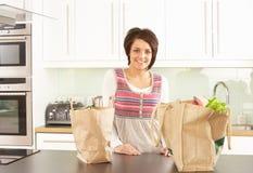 Giovane donna che disimballa acquisto nella cucina moderna Fotografie Stock