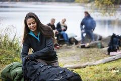 Giovane donna che disimballa zaino al campeggio fotografia stock