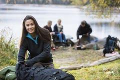 Giovane donna che disimballa zaino al campeggio fotografie stock