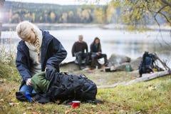 Giovane donna che disimballa zaino al campeggio fotografia stock libera da diritti