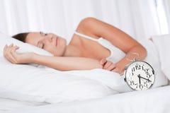 Giovane donna che dorme nella base con la sveglia Fotografia Stock