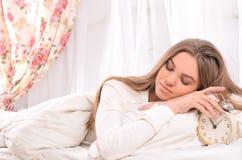 Giovane donna che dorme nella base con la sveglia Fotografia Stock Libera da Diritti