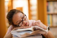 Giovane donna che dorme nella biblioteca Fotografie Stock