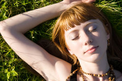 Giovane donna che dorme su un'erba verde fotografia stock libera da diritti