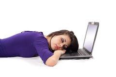 Giovane donna che dorme sul computer portatile Immagini Stock