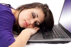 Giovane donna che dorme sul computer portatile Fotografie Stock Libere da Diritti