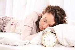 Giovane donna che dorme sul letto e sulla sveglia Immagini Stock