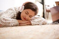 Giovane donna che dorme sul pavimento e che ascolta la musica con le cuffie Fotografie Stock