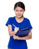 Giovane donna che effettua ricerca con la lavagna per appunti Fotografia Stock