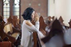 Giovane donna che elemosina perdono in chiesa fotografia stock libera da diritti