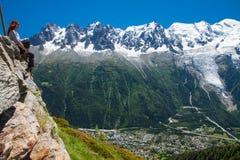 Giovane donna che enjoing la vista al villaggio di Charmonix, alpi francesi a Immagini Stock