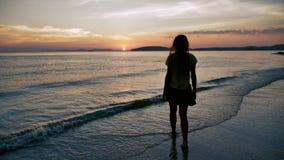 Giovane donna che entra in mare al rallentatore al tramonto su una spiaggia tropicale archivi video