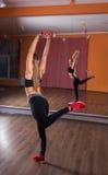 Giovane donna che equilibra su una gamba nello studio di ballo Immagini Stock Libere da Diritti