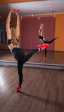 Giovane donna che equilibra su una gamba nello studio di ballo Immagine Stock