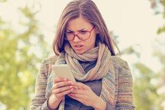 Giovane donna che esamina arrabbiata il telefono fotografie stock