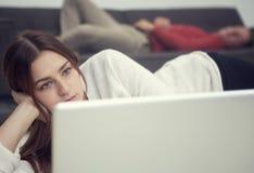 Giovane donna che esamina computer portatile ed uomo che si trovano sullo strato in backgrou Fotografia Stock Libera da Diritti
