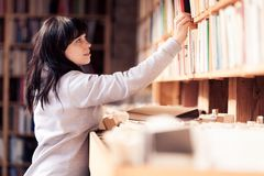 Giovane donna che esamina i libri in una libreria Immagini Stock Libere da Diritti