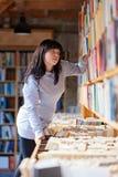 Giovane donna che esamina i libri in una libreria Fotografia Stock Libera da Diritti