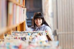 Giovane donna che esamina i libri in una libreria Fotografie Stock Libere da Diritti